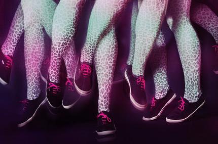 een zwarte achtergrond waarop je vijf keer hetzelfde paar benen op en neer ziet springen. De benen zijn in grijs witte panter print en hebben zwarte gympen met roze veters
