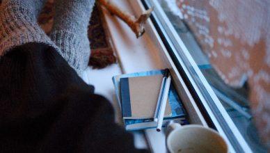 Benen met wollen sokken in een vensterbank. Rechts zie je een gehakt gordijntje, twee notitieboekjes en een leeg koffiekopje