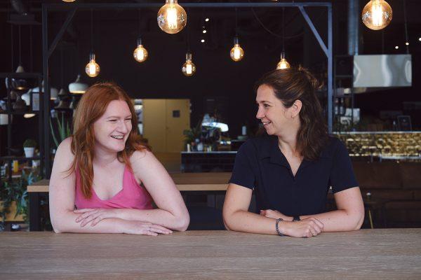 Anne-Loes zit links, heeft rood lang haar en een roze jurkje. Ze lacht richting Esmeralda die rechts zit. Ze heeft donker haar en een donkerblauw shirt. Ze kijkt lachend naar Anne-Loes